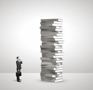 business_man_looking_at_large_stack_of_books.jpg